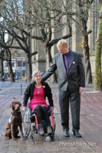 Media 025 199x300 - Couple on a city sidewalk with their service dog