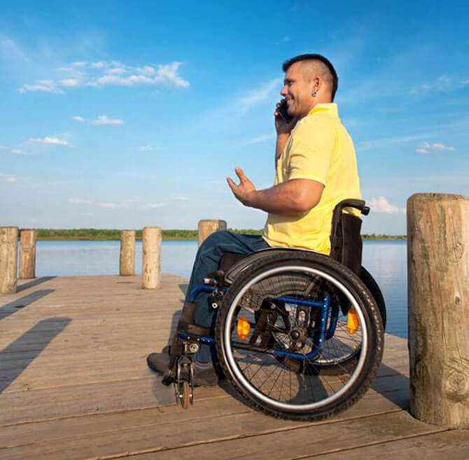 a disabled guy sitting in a wheelchair and talking on the phone on a beach