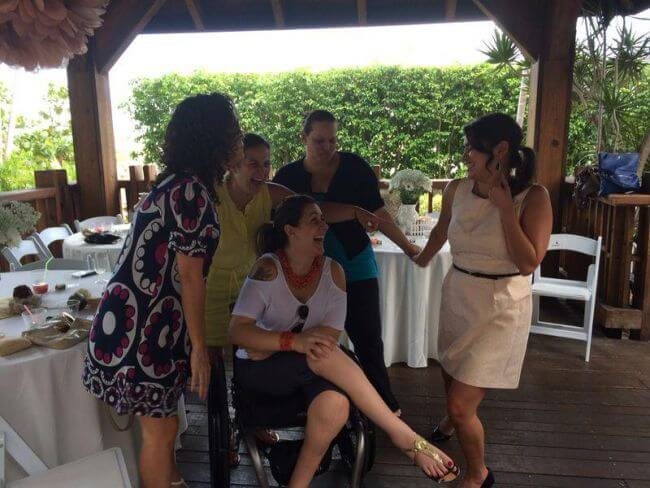 image of a group of women laughing and talking with one of them sitting on wheelchair