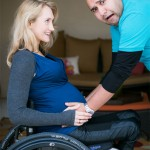 Ali pregnant and in a wheelchair with her husband in a blue shirt standing and holding her stomach