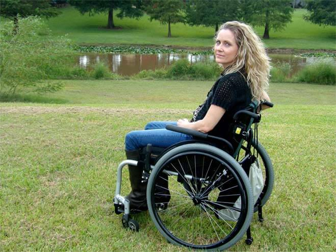 beautiful disabled woman with blonde hair sitting in the park in her wheelchair