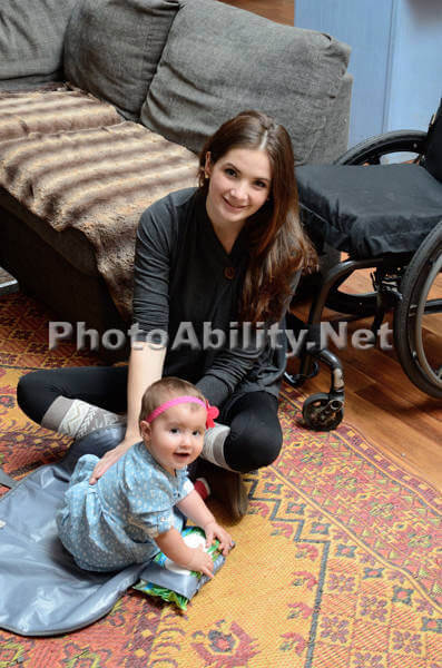 image of a young mother sitting on floor playing with her baby with a wheelchair beside her
