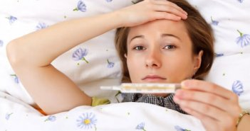 image of a girl laying on a bed with one hand on her forehead while holding a thermometer from other hand