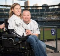 image of a man and a disabled woman sitting on his lap looking happy