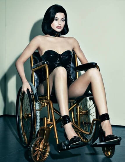 image of kylie jenner sitting in a hot black dress on a wheelchair