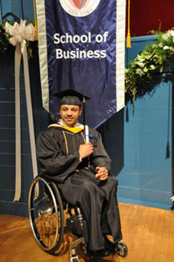 image of a man sitting on a wheelchair in black graduation gown and cap carrying a degree
