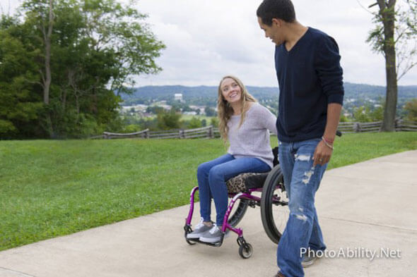 image of a woman sitting on a wheelchair holding hands with her boyfriend walking beside her