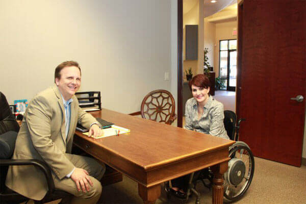 Author sitting in wheelchair sitting at desk with man in suit across from her