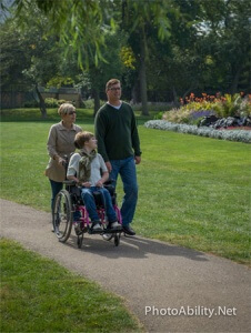 Mother and Father walking daughter in wheelchair thru park 226x300 - Mother-and-Father-walking-daughter-in-wheelchair-thru-park
