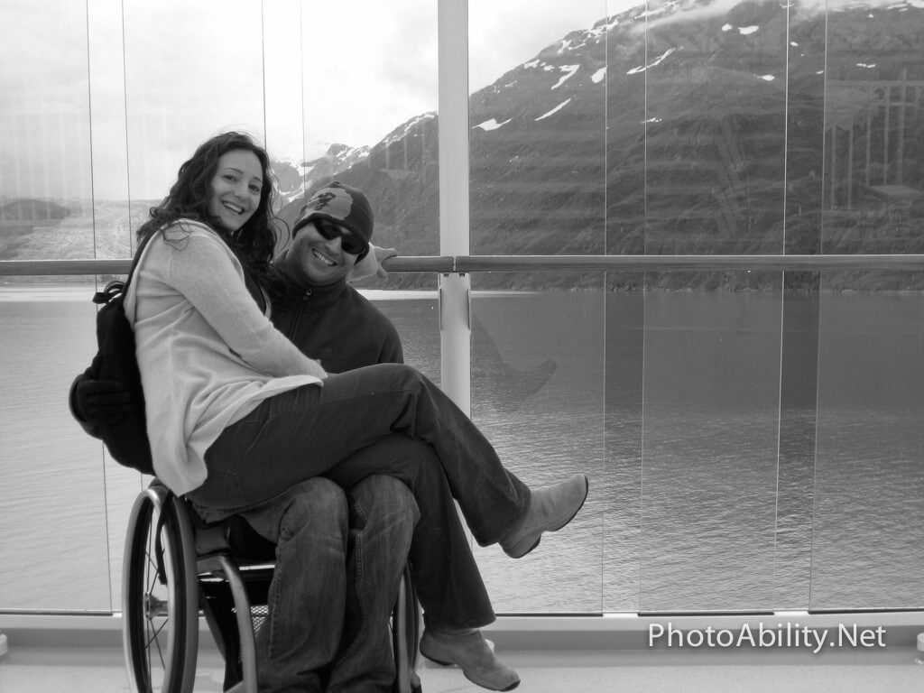 Man in wheelchair with girlfriend on lap on a boat on deck in cold weather