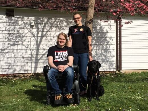 Casey, a young man with blonde hair in wheelchair with a young girl posing next to him outside in the sun with his black labrador