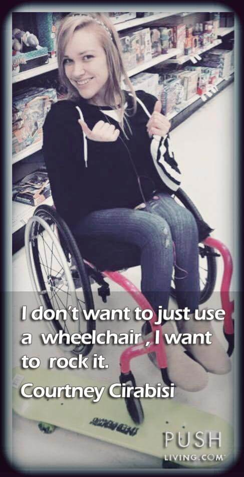 a beautiful girl sitting on a wheelchair smiling and doing thumbs up with a skate board beside her wheelchair