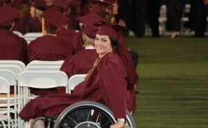a girl on a wheelchair wearing maroon graduation gown and cap