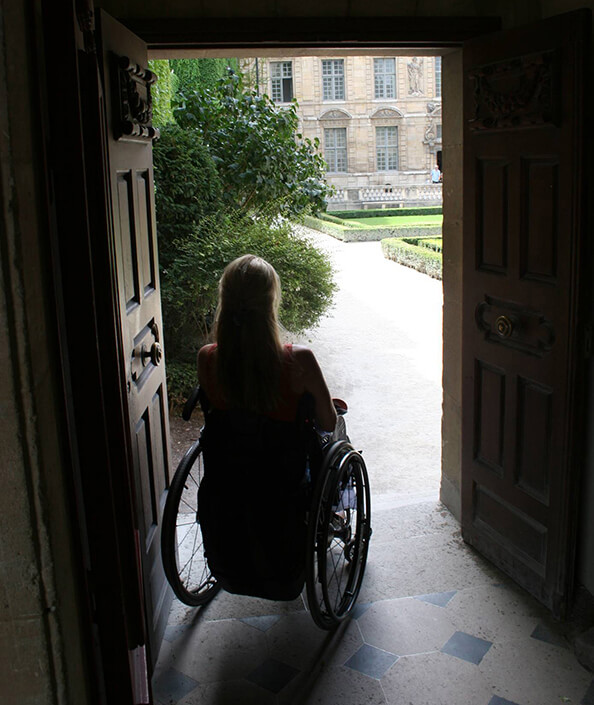 Woman in wheelchair sits in dark room looking out door to outside courtyard