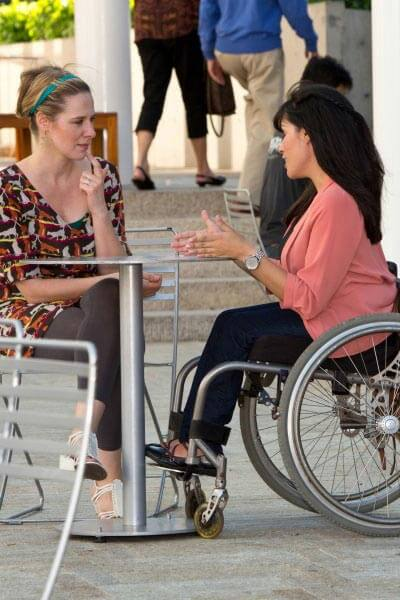 woman sitting in wheelchair in an outdoor patio talking to a woman at table