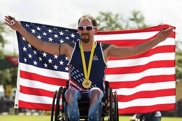 Man in wheelchair holding American flag with medal