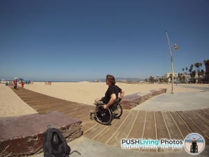 Paraplegic man in beach wheelchair looking at the ocean and people 300x225 - Beach Wheelchairs: Making Summer Fun Accessible for ALL