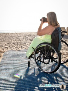Paraplegic woman in wheelchair taking photos on beach 224x300 - Beach Wheelchairs: Making Summer Fun Accessible for ALL
