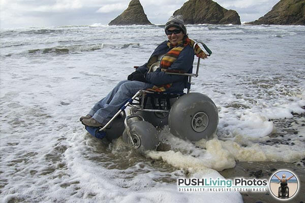 a disabled woman sitting on a beach wheelchair at beach and smiling
