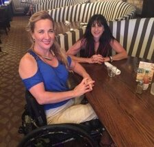 A woman and a girl sitting in wheelchair accessible booths