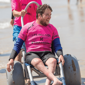 paraplegic man in all terrain wheelchair 300x300 - Summertime Fun and Fitness: Upcoming Adaptive Surf Events with Life Rolls On