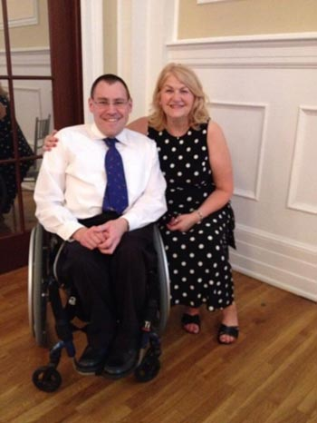 A man on a wheelchair wearing a suit, with a women in black and white polka dotted dress, beside him.