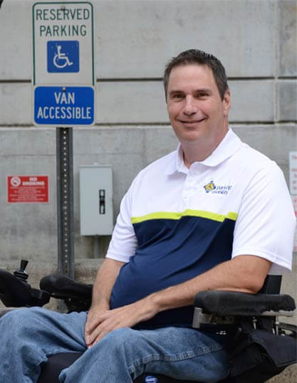 A guy in a wheelchair in a blue and white t-shirt, with a yellow strip, smiling at the camera