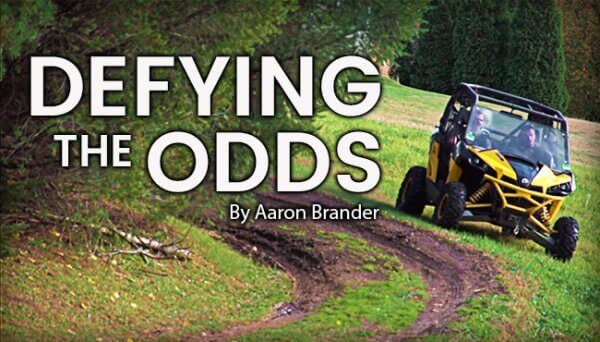 A defying the odds quote on a picture showing a go-cart and nature