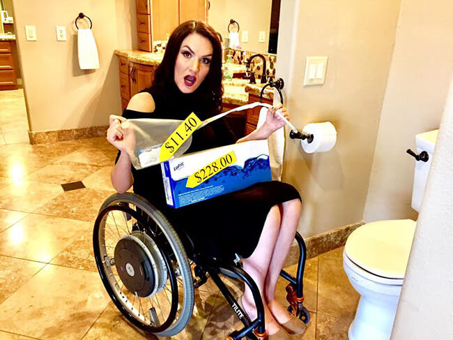 a girl holding catheter showing price while sitting on her wheelchair