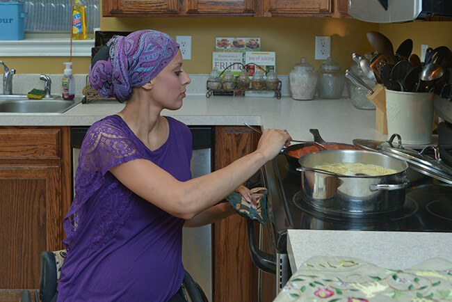 image of woman formulating essential oil in a pan in kitchen