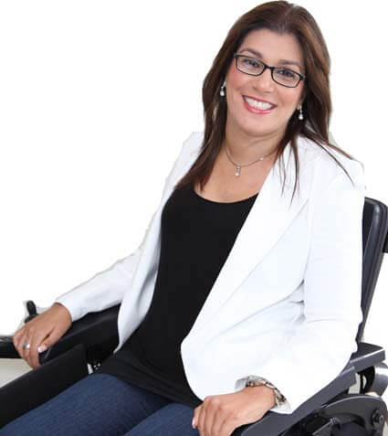 A women sitting on a wheelchair wearing a black shirt with white quote smiling at the camera
