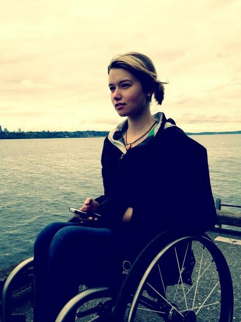 young disabled girl in her wheelchair near a lake front