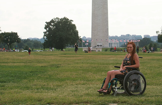 image of beautiful woman sitting on a wheelchair and smiling in a garden