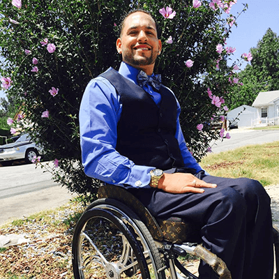 image of a disabled man sitting on a wheelchair and smiling at a country road