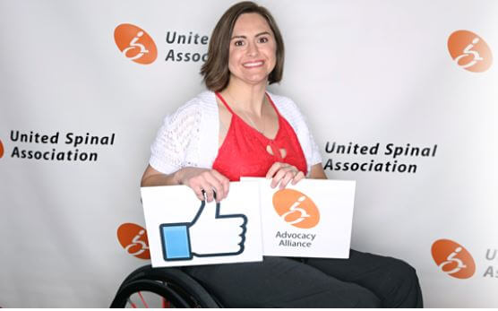 women sitting on a wheelchair smiling while holding advocacy alliance and thumbs up placards