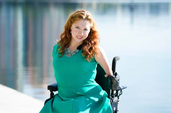 image of a handicapped woman sitting on a wheelchair and smiling near a lake