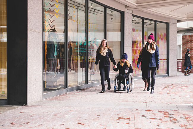 teenage girl sitting on a wheelchair out on winter Christmas shopping with her friends
