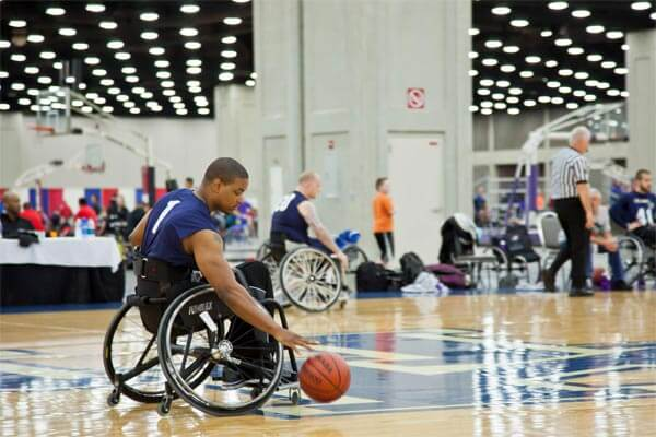 man in wheelchair playing basketball at indoor court