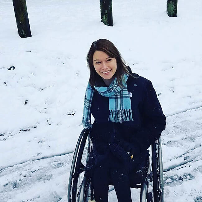 young disabled woman in a wheelchair wearing a blue scarf playing in the snow and smiling