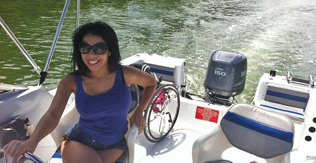 Women on a boat sitting near a wheelchair and smiling
