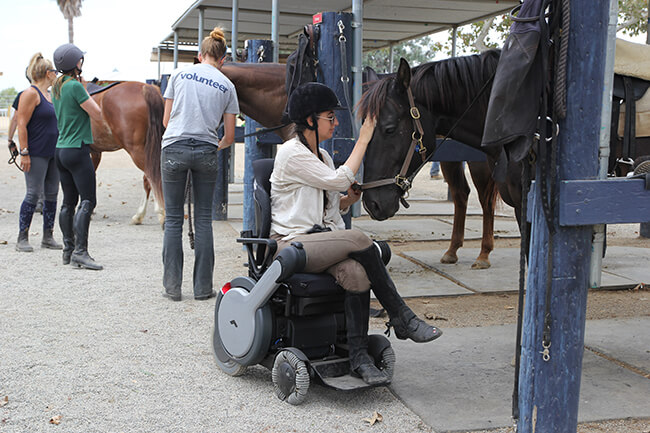 girl shown in riding gear and hat in a white WHILL pwer wheelchair petting dark horse