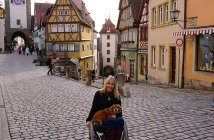 """Kelly in courtyard in Rothenburg, Germany in her """"cobblestone chair"""" that her husband outfitted with big wheels and castors."""