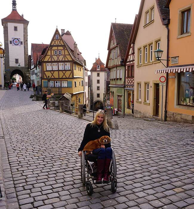"Kelly in courtyard in Rothenburg, Germany in her ""cobblestone chair"" that her husband outfitted with big wheels and castors."