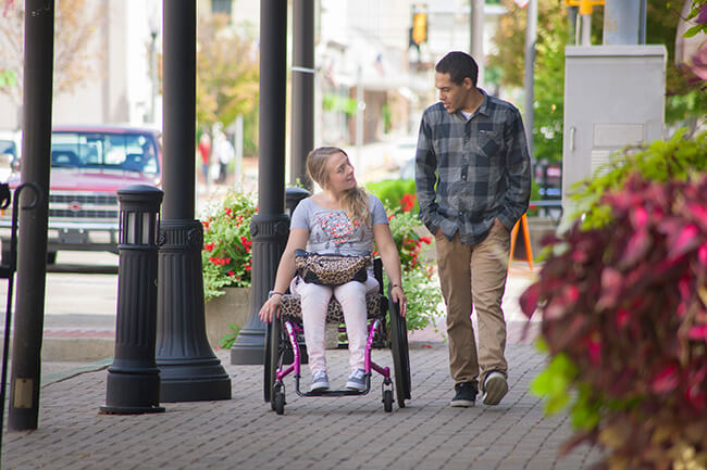 woman on a wheelchair talking to a man