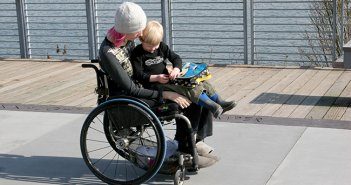 image of a disabled woman on a wheelchair with her son sitting on her lap