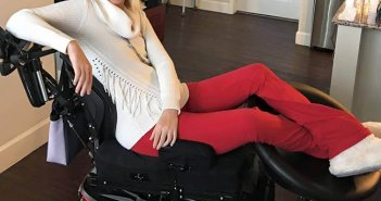Ali seen in an electric wheelchair posing in red pants and white sweater
