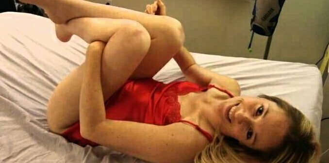 Ali lying in bed posing with her legs up to her chest in a red lingerie smiling and looking into the camera