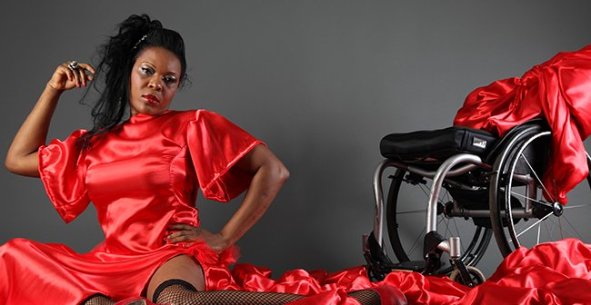 A women in a red dress sitting beside a wheelchair