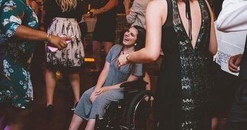 Women in a wheelchair on the dance floor laughing along with the crowd
