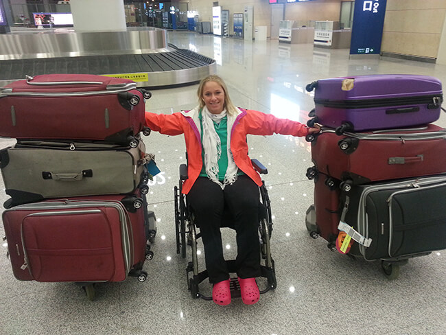 Disabled girl in a wheelchair at the airport with her luggage